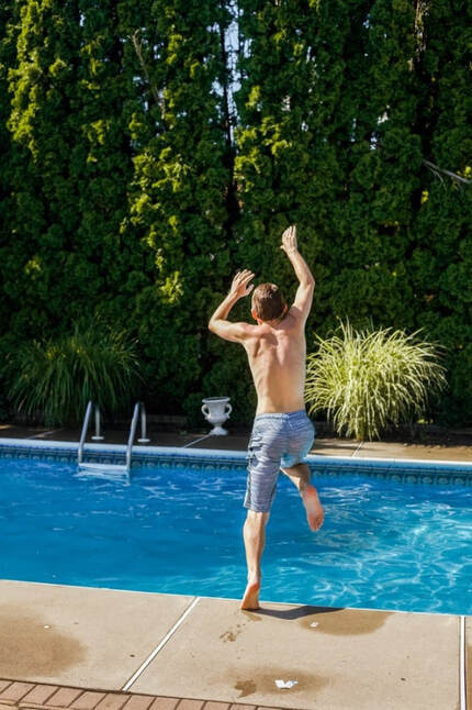 Boy jumping in to a pool